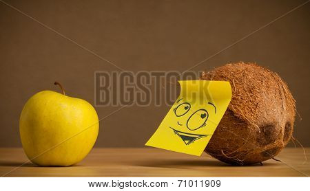 Coconut with sticky post-it note reacting at apple