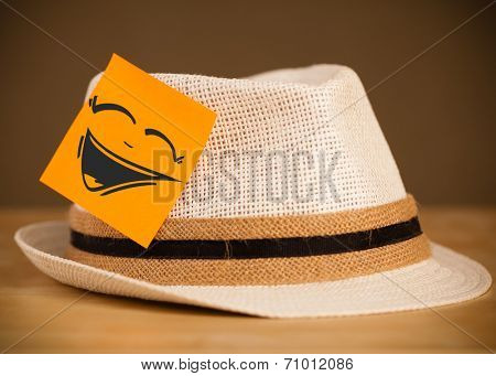 Drawn smiley face on a post-it note sticked on a hat