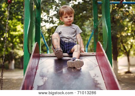 Adorable Little Boy Playing On A Slide