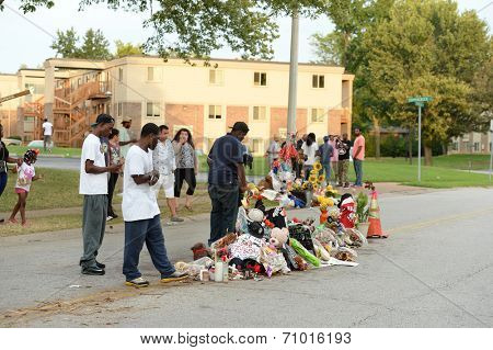 FERGUSON, MO/USA - AUGUST 30, 2014: A group gathers at makeshift memorial where black teenager Michael Brown was shot to death by police in Ferguson, Missouri.