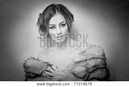 Attractive sexy young woman wearing a fur coat posing provocatively indoor. Black and white portrait