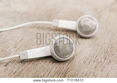 Modern Portable Audio Earphones On Wood