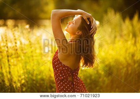Happy Long-haired Woman At Sunset In The Field