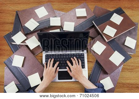 Student Typing With Laptop Around Book 1