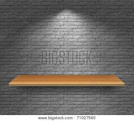 Empty wood shelf on dark brick background.
