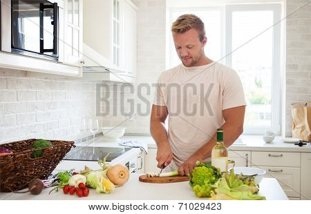 Handsome Man Cooking At Home Preparing Salad In Kitchen