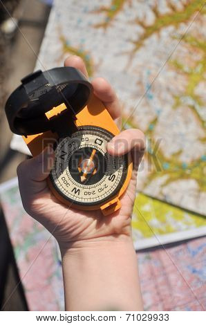 Compass In His Hand On The Topographic Maps.
