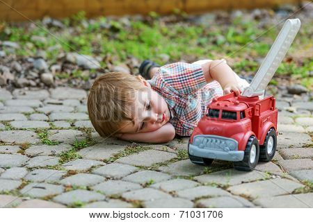 Toddler Playing With A Toy Fire Truck Outside - Series 5