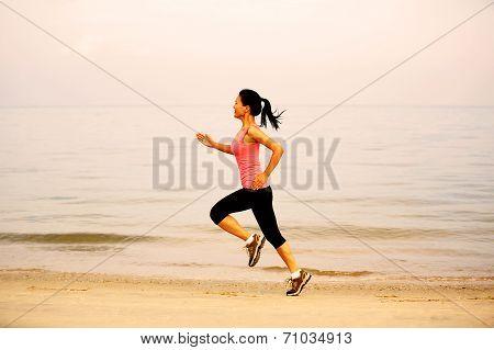 sports woman running seaside beach