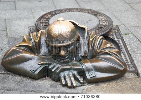 BRATISLAVA, SLOVAKIA - JUNE 25, 2014: Cumil (The Watcher) - famous statue of man peeking out from under a manhole cover. It was made in 1997 by Viktor Hulik