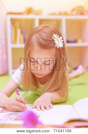 Cute little girl lying down on the floor and drawing picture to the album, having fun at home, happy childhood, having art talent concept