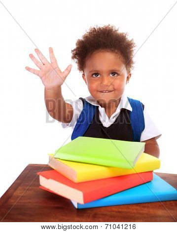 Happy African preschooler sitting behind desk with many books on it, isolated on white background, raised up hand and say hello, back to school concept