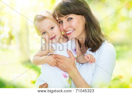 Beautiful Mother And Baby playing in a park. outdoors. Nature. Beauty Mum and her Child playing outdoors together. Outdoor Portrait of happy family. Joy. Mom and Baby