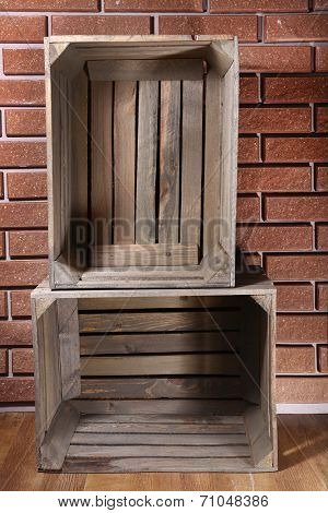 Rectangular wooden boxes on the floor in front of brick wall