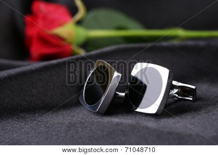 Pair of cuff links with red rose on black silk fabric background
