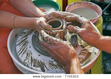 Potters' Hands Guiding Woman's Hands