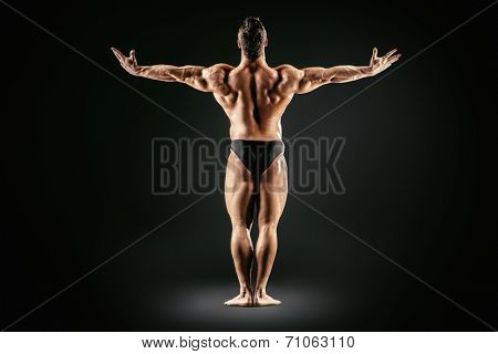 Beautiful muscular man bodybuilder posing back over dark background. Full length.