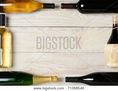 High angle shot of a group of wine bottles on a rustic white wood table. The bottles are laying on their sides and end to end to form a rectangle frame with a blank center.