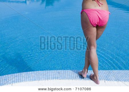 Woman In Pink Bikini And Pink Hat By Swimming Pool.