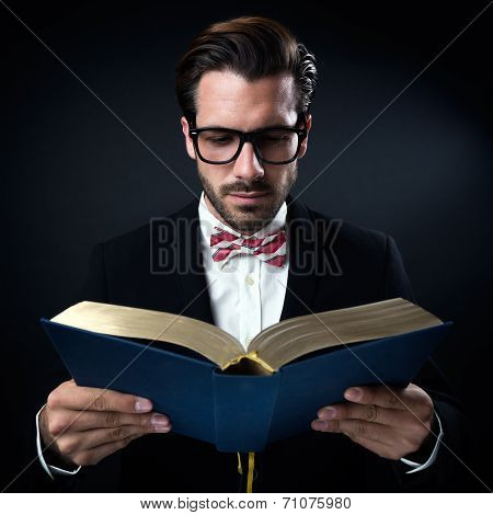 Intrigued Businessman With Glasses Reading A Book. Isolated On Black.