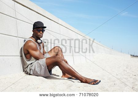 Handsome Guy With Headphones And Sunglasses Sitting On Beach