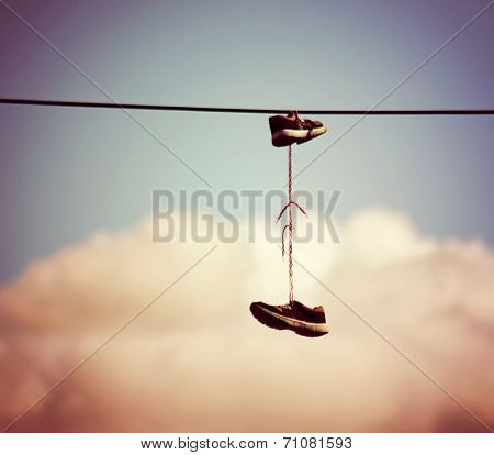 sneakers hanging from electrical wire against a blue sky with clouds toned with a retro vintage instagram filter effect