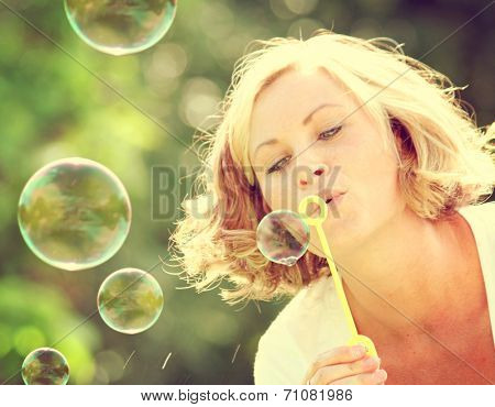 a pretty girl blowing bubbles toned with a retro vintage instagram filter effect