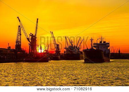 Silhouette Of Sea Port Cranes Over Sunset