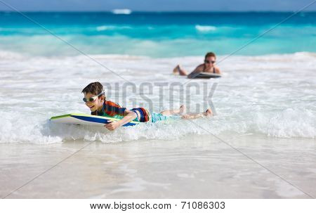 Mother and son n vacation having fun swimming on boogie board