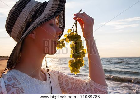 Portrait of sexy girl in hat holding grapes