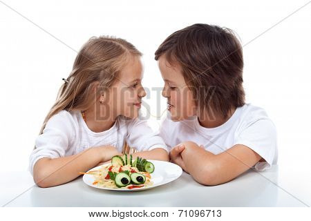 Kids sipping on the same string of pasta - sharing a plate of healthy food, isolated