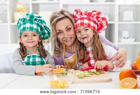 Happy chefs in the kitchen - woman and little girls portrait preparing fruit salad