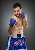picture of muay thai  - Caucasian kickboxer or muay thai fighter executing a punch on gray background - JPG