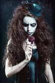 stock photo of clown rose  - Woman in image of a gothic freak clown with withered flower - JPG