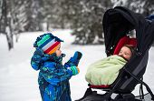 image of blanket snow  - A little boy in a snowsuit is looking at a baby bundled in a baby stroller outside in the snow. ** Note: Shallow depth of field - JPG