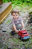 stock photo of fire truck  - A toddler playing with a toy fire truck outside in the summer - JPG