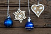 picture of ginger bread  - Two Ginger Bread Cookies and two blue Christmas Balls Hanging on Wood as Christmas or Winter Background - JPG