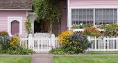 picture of black-eyed susans  - The entrance to an old Victorian home next to a matching cottage behind a white wooden gate with bright yellow black eyed Susans - JPG