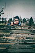 stock photo of barricade  - Senior man aiming a gun at you and hiding behind barricade outdoors - JPG