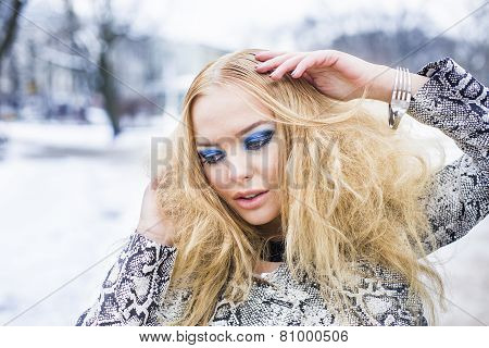 Blonde lady is posing in the winter