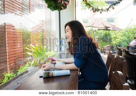 Young Business Asian Woman Having A Coffee Break And Reading Magazine