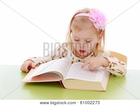 Little girl reading a book with enthusiasm.