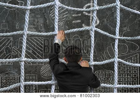 Businessman Climbing Crisscross Rope Net On Business Concept Doodles Background