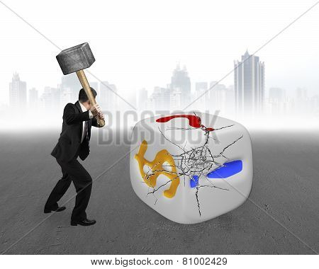 Businessman Holding Sledgehammer Hitting Large Dice With Gray Cityscape