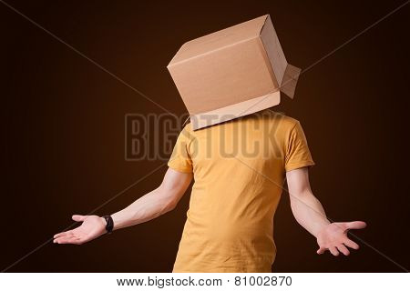 Young man standing and gesturing with a cardboard box on his head