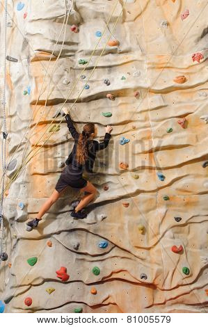 Businesswoman climbing on man-made cliff in the sport centre