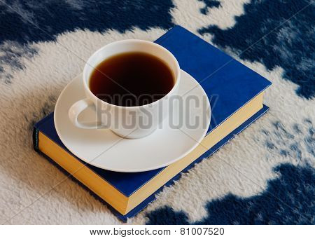 Cup Of Tea And Book On The Blanket