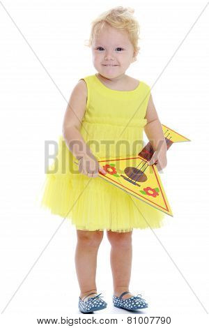 Adorable little girl in autumn coat holding a bouquet of maple l