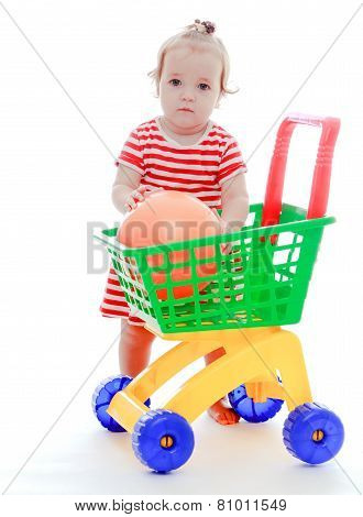 The little girl puts a great ball into the toy truck.