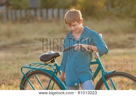 Portrait Of Teenager With Retro Bike In Farm Field